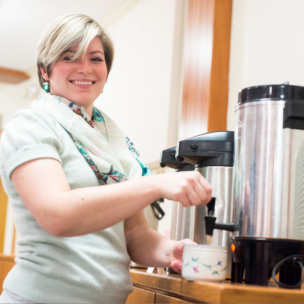 School of Divinity student pours a cup of coffee during weekly coffee hour