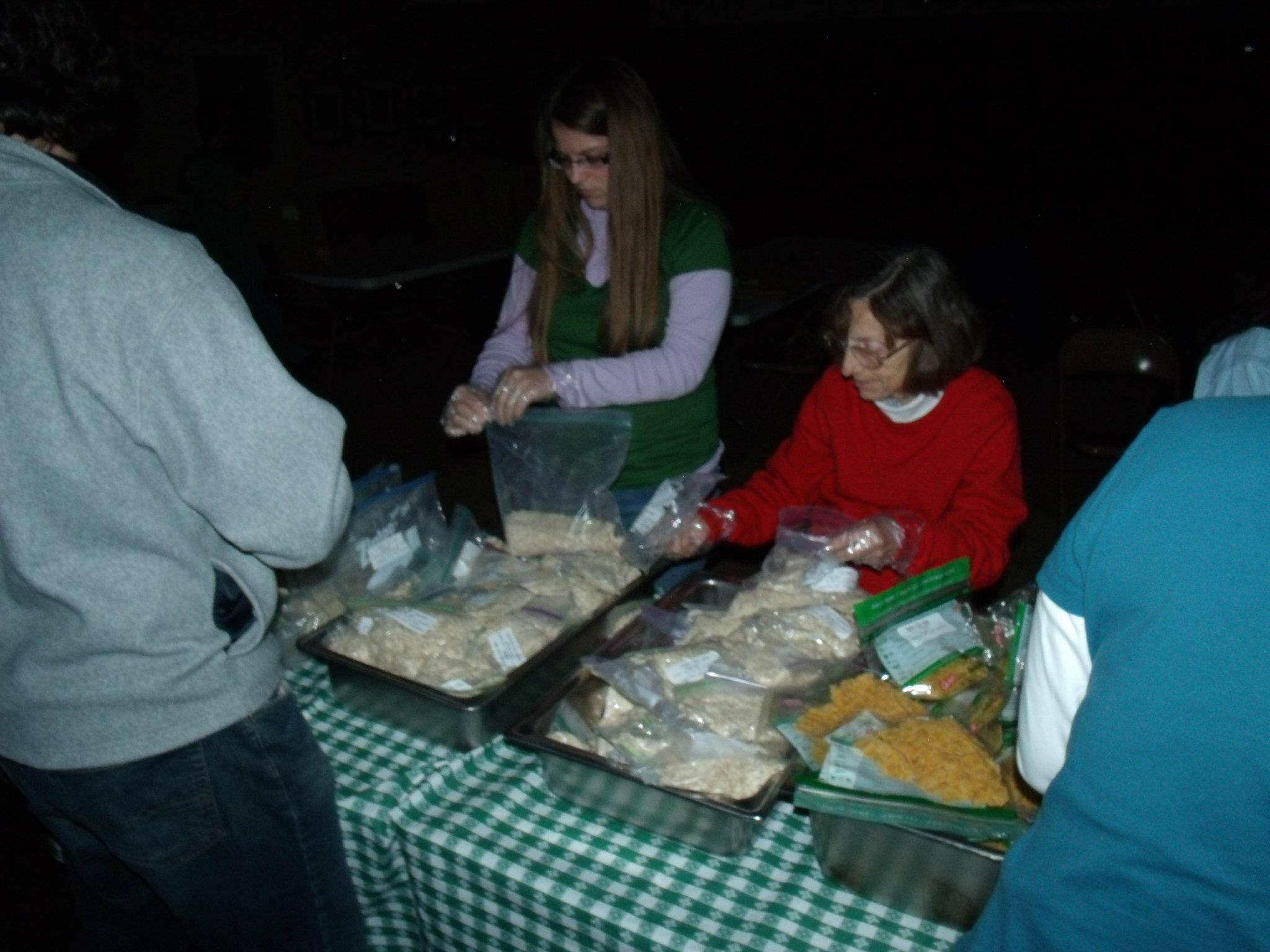 Rev. Cheek (right) and Russell (left) serve a meal to residents in a community during the 2012 travel course