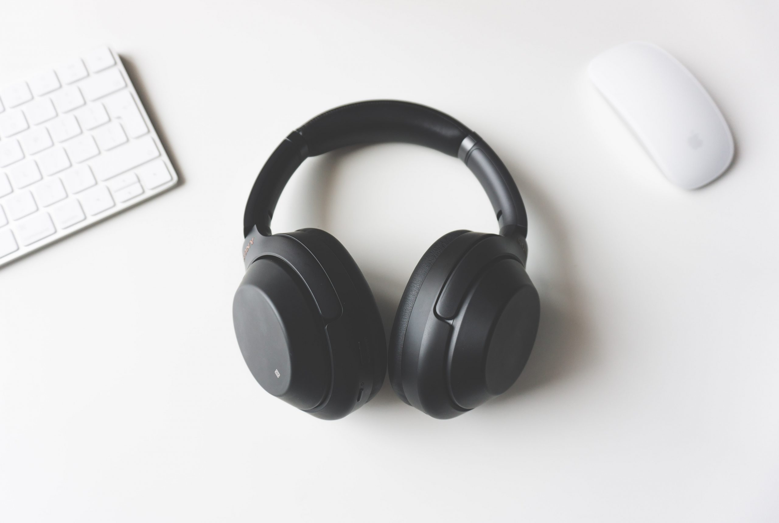 image of black headphones surrounded by a keyboard and mouse on a white background. Photo by Tomasz Gawlowski on Upsplash.