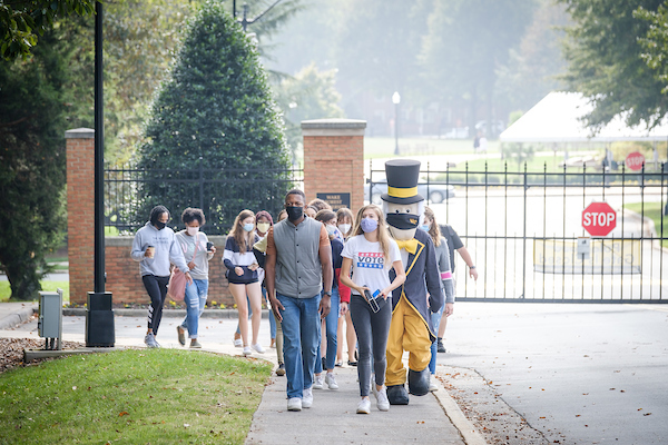 Wake Forest students gather and march to an early voting site across the street from campus on Thursday, October 15, 2020. The Demon Deacon mascot joins the march.