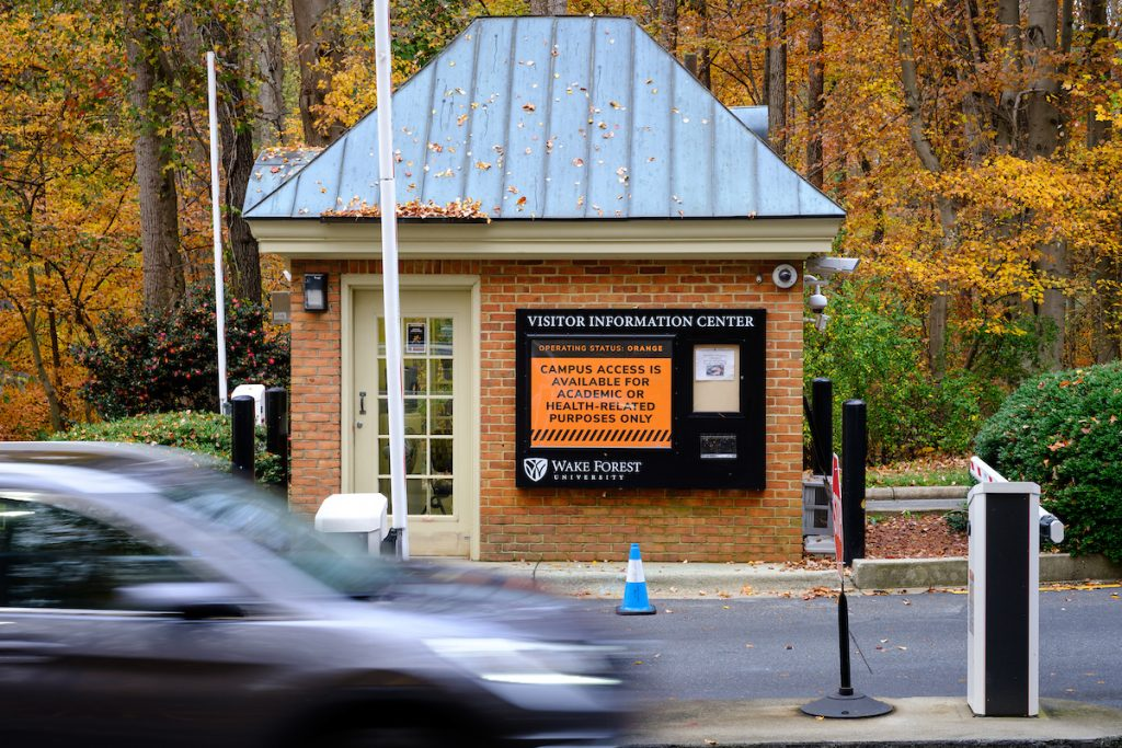 The gatehouse at the Reynolda Road entrance to Wake Forest shows the current Operating Status Orange level as cars enter, on the campus of Wake Forest University, Tuesday, November 10, 2020.