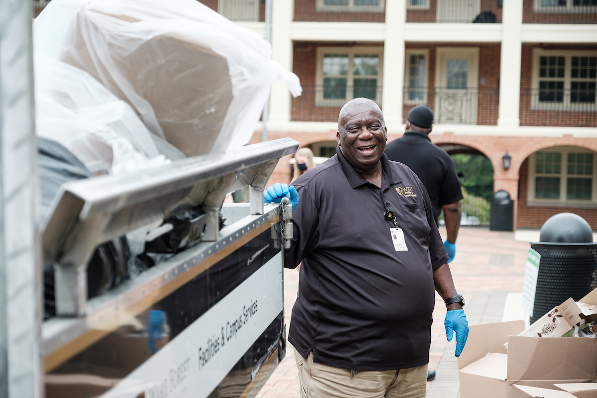 Wake Forest facilities team member Ernie Johnson collects trash outside Taylor Residence on Thursday, August 20, 2020.