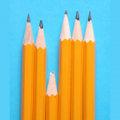 Image of 6 pencils in a row on a blue background. Five of the pencils are long and sharpened, but the third pencil in the row is short and has a broken tip.