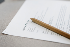 """Picture of a pencil sitting on top of a stapled set of paper with """"Syllabus, Fall 2016"""" written on top and the Time of Day, Location, Instructor, and Contact Info visible."""