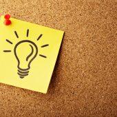 Lightbulb on post it note on bulletin board