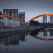 Bridge against black and white cityscape