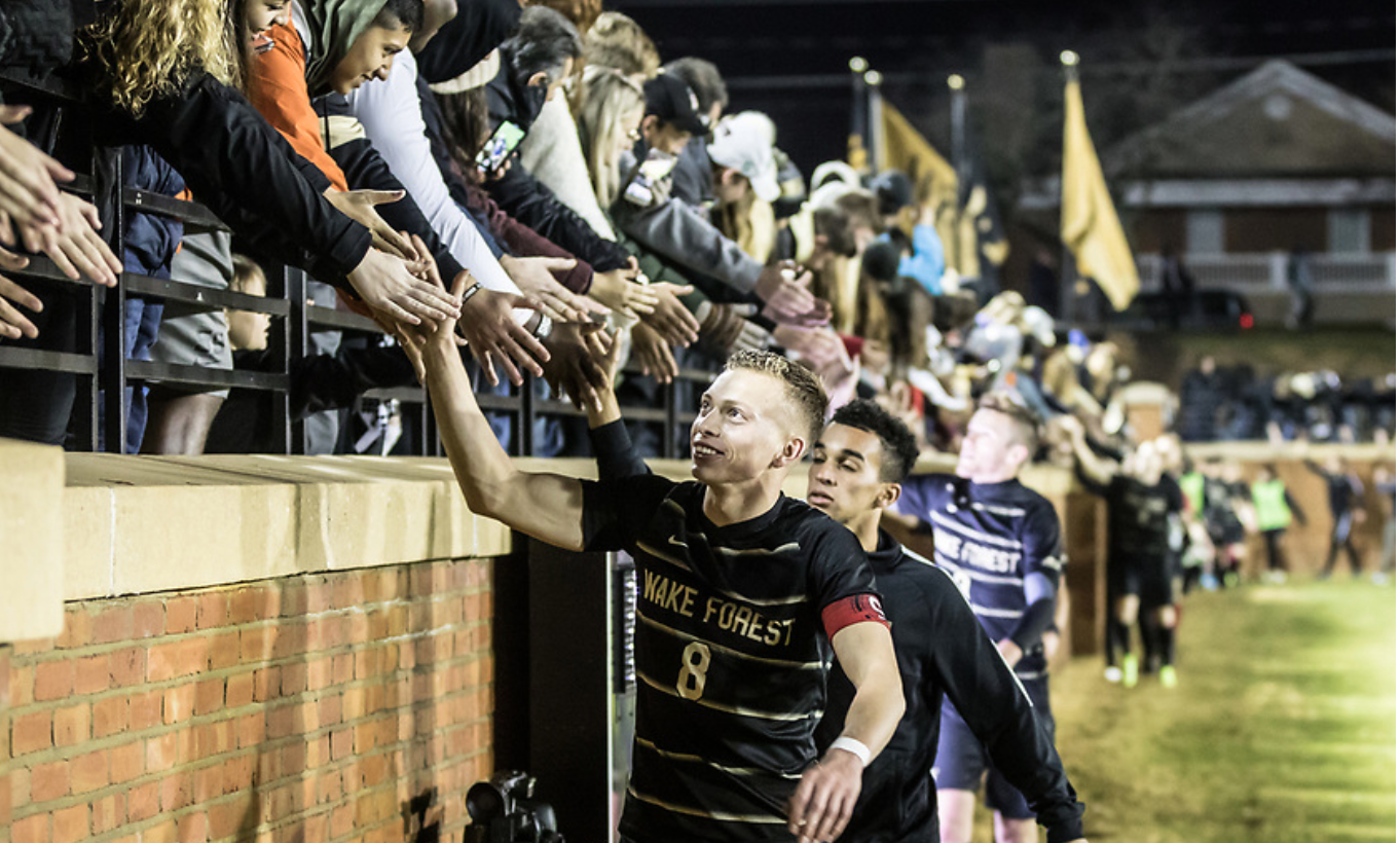 WFU Men's Soccer high-fiving with fans after a game