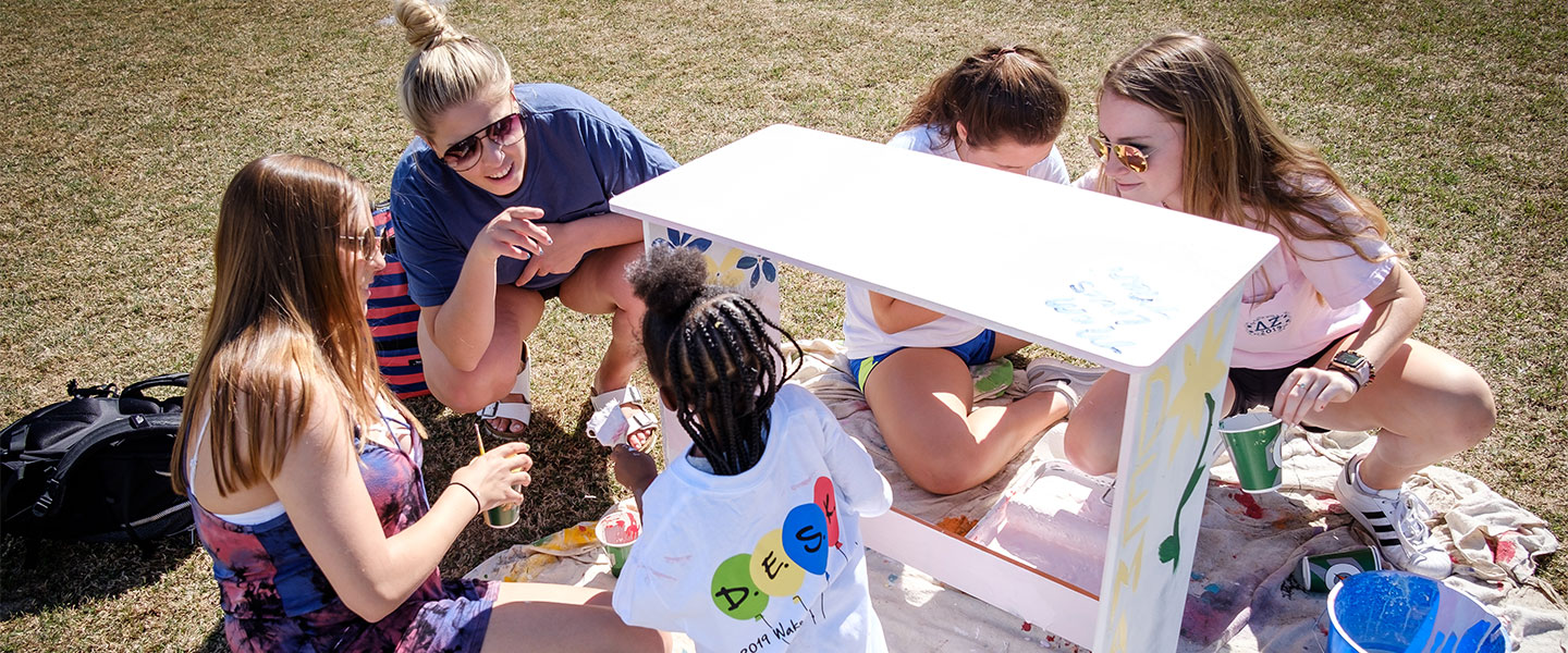 Wake Forest students paint desks for local elementary school students at the annual volunteer service project DESK
