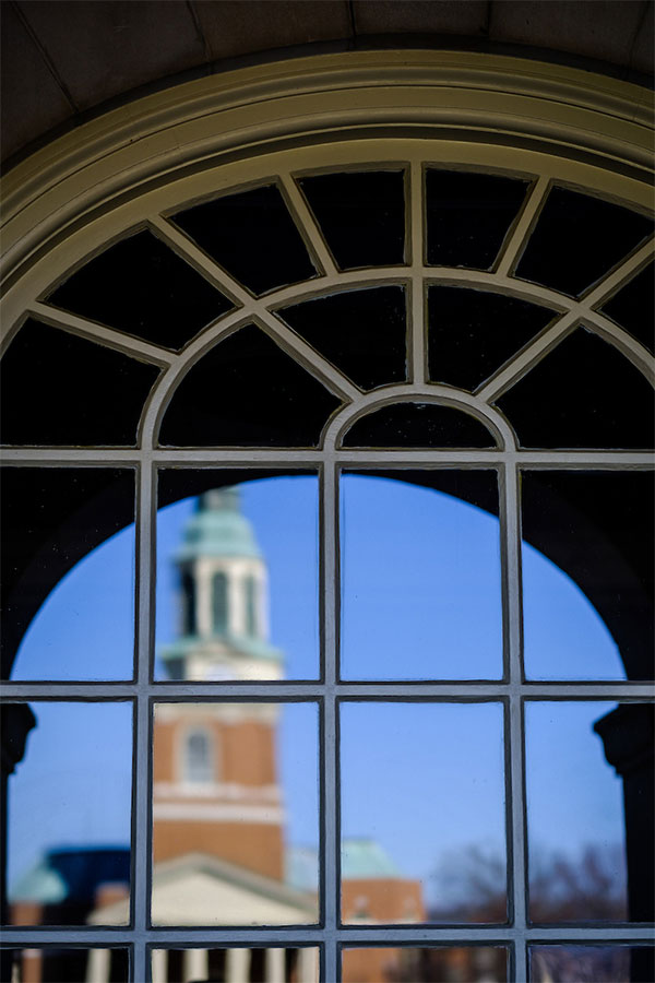 The bell tower of Wait Chapel is reflected in a window in Reynolda Hall