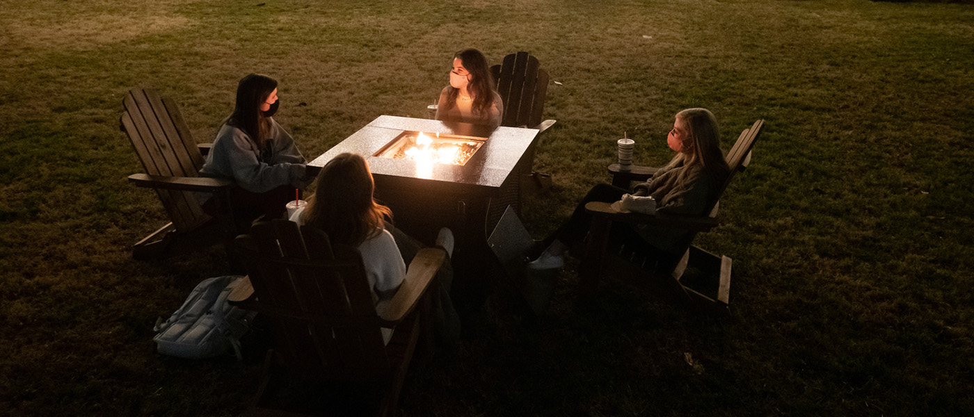 Students around a firepit at night