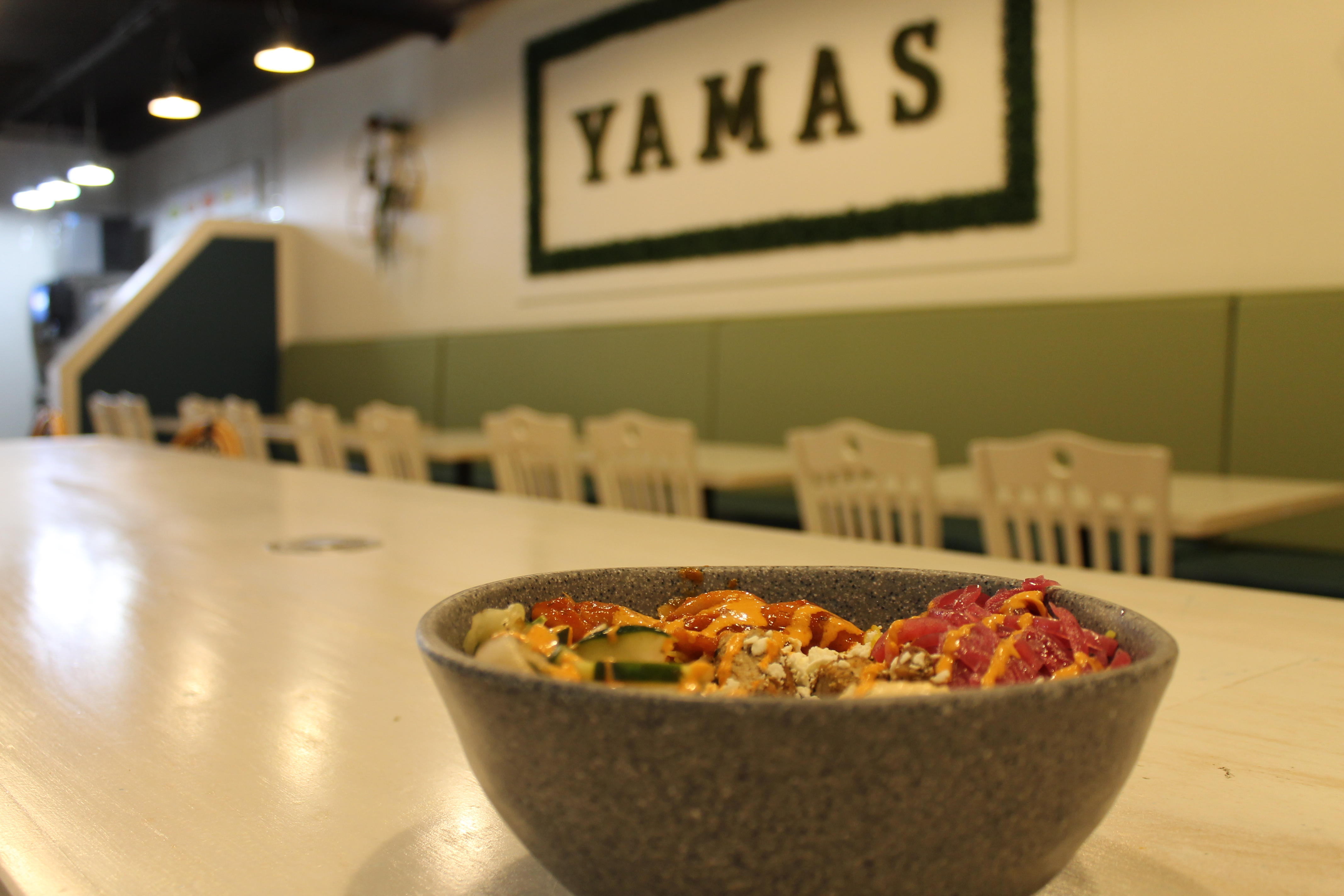 Chicken and rice bowl on table with yamas sign in background