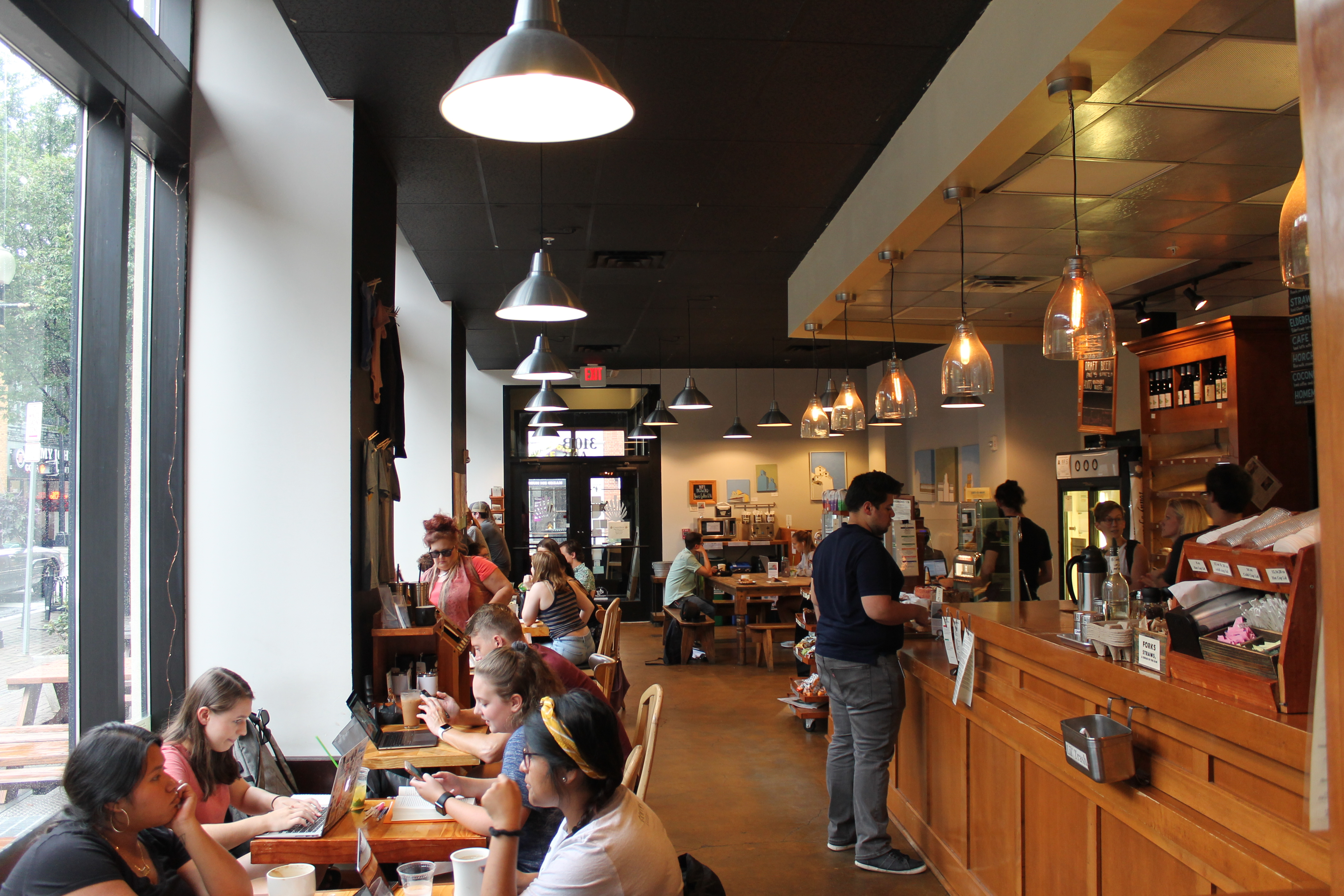 Interior of camino bakery, people sitting by windows and ordering at counter