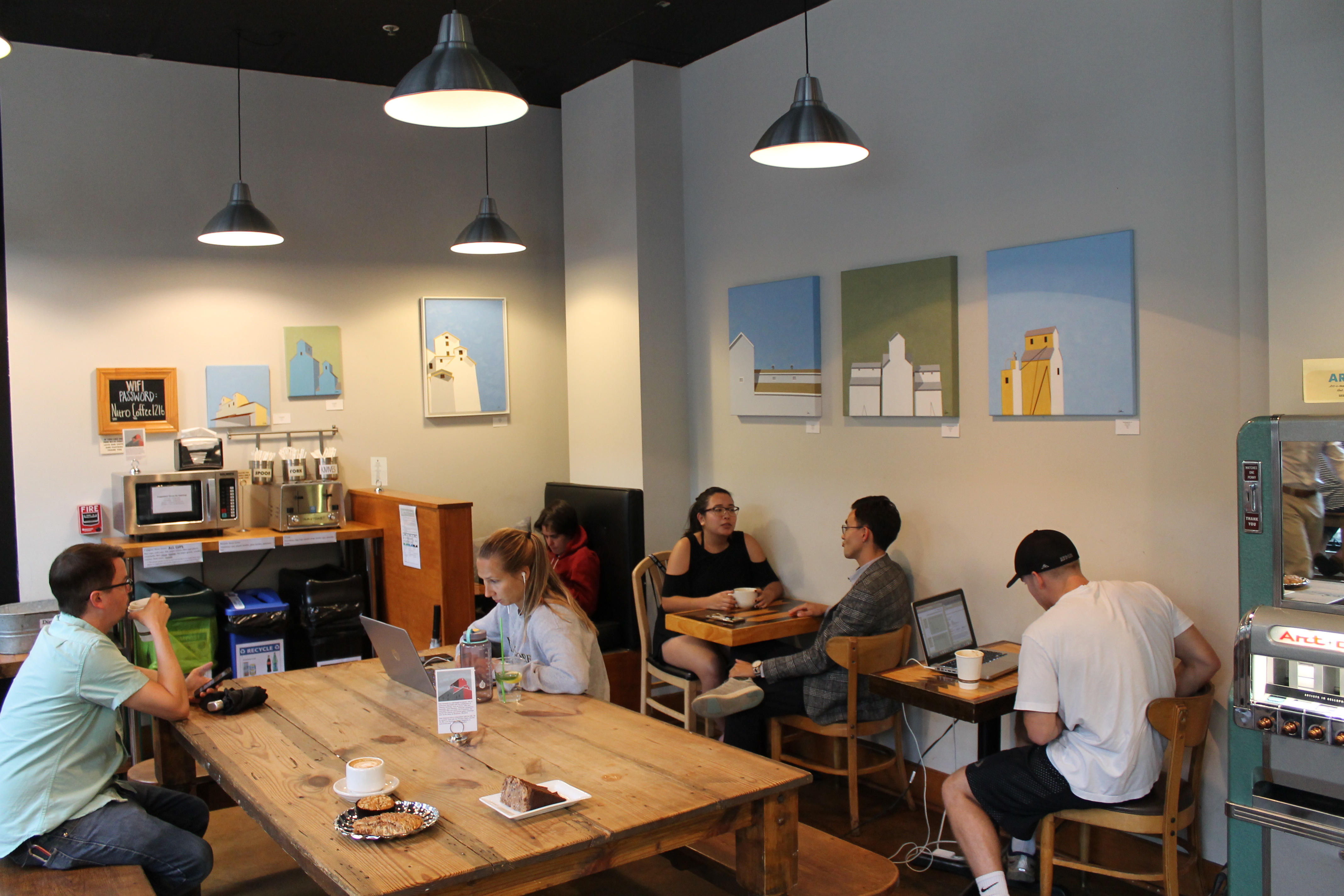 Interior of camino bakery, people sitting by paintings and art machine