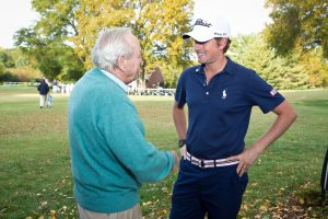 Palmer talks with PGA TOUR golfer Webb Simpson during Wake Forest's Pro-Am golf tournament in 2011.