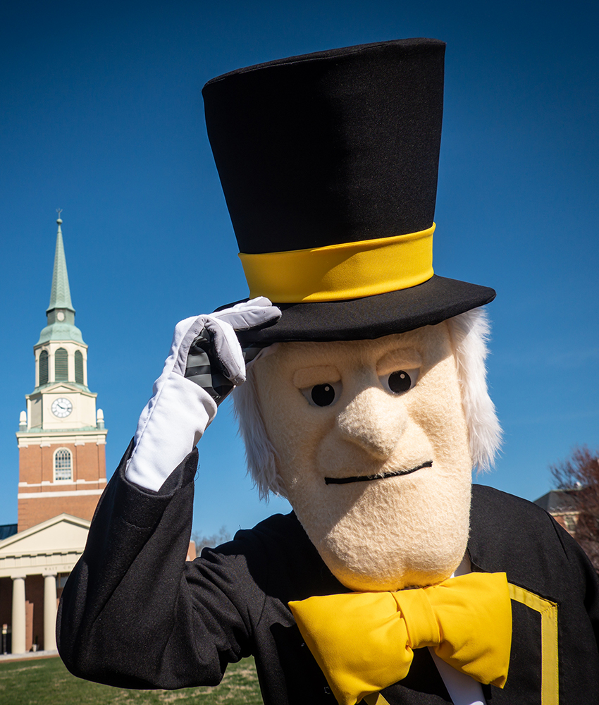 The Demon Deacon tips his hat standing in front of Wait Chapel