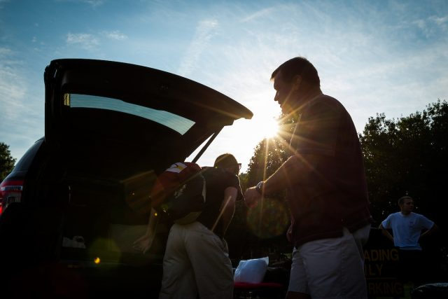 Students loading the car as the sun sets.