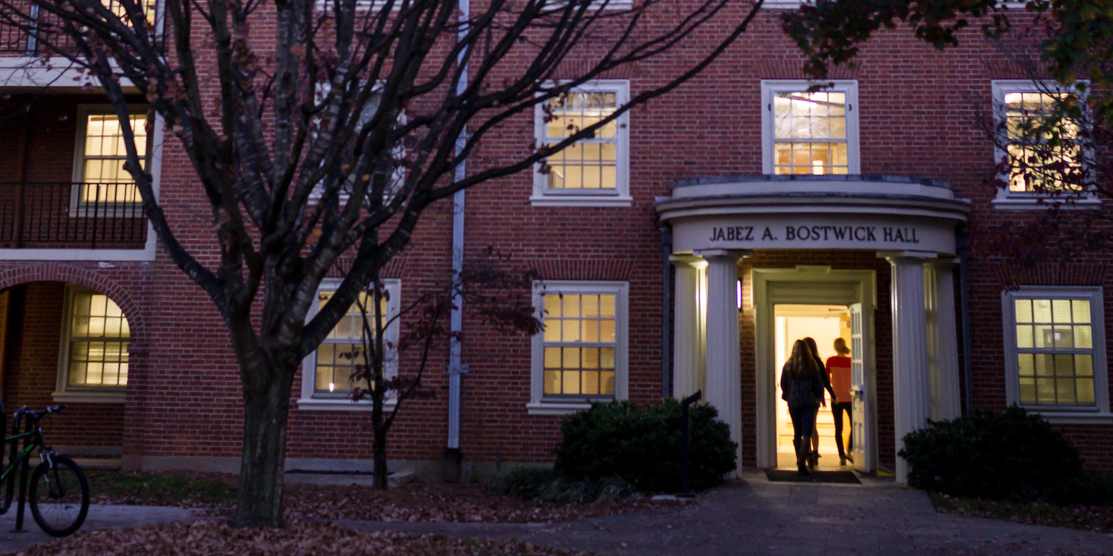 Silhouette of student entering Bostwick residence hall at night