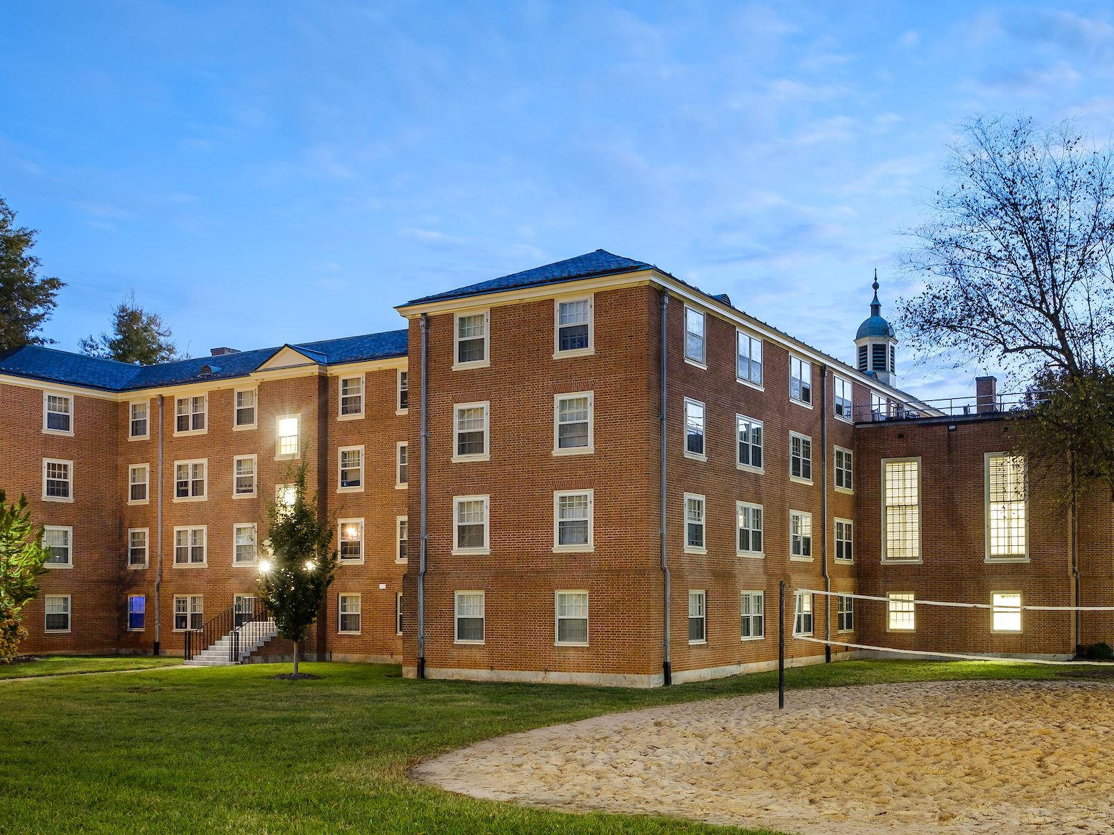 Volleyball court and rear view of Johnson residence hall