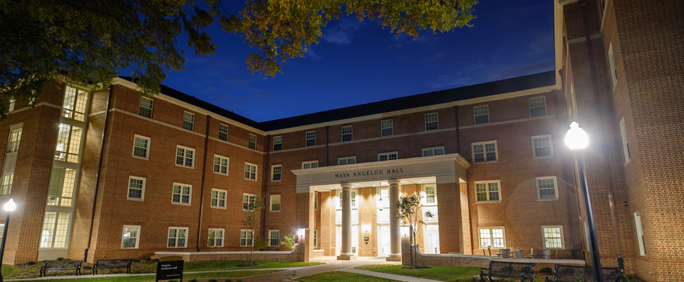 Exterior photo of the entrance to Angelou Residence Hall at night