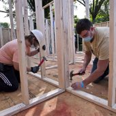 Americorps worker Julia Haynes and Wake Forest senior engineering student Goren Jovanovic nail pre-built walls.