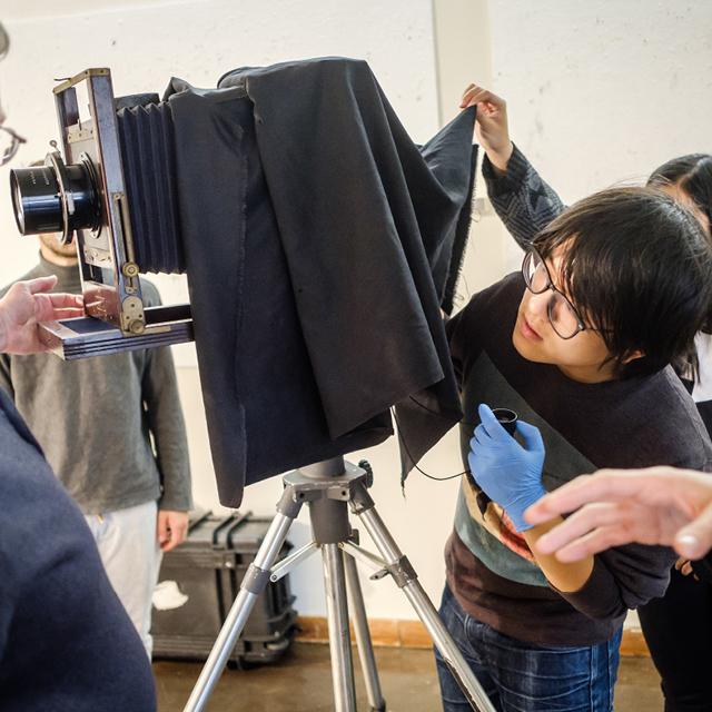 Student using tintype camera equipment