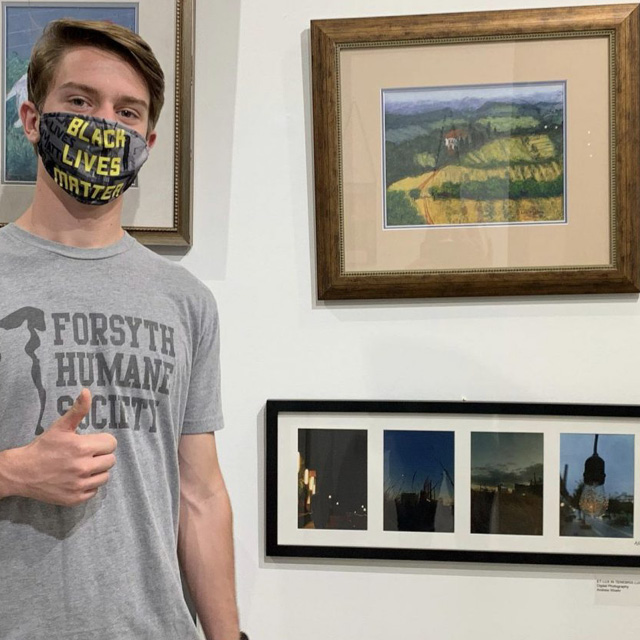 student in front of art
