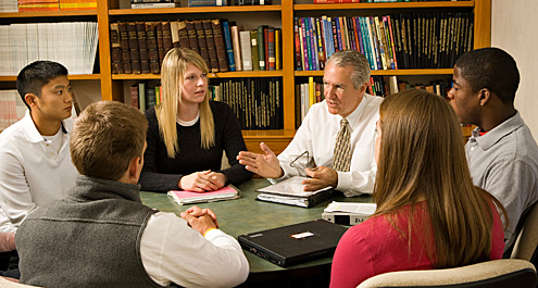 Photo of classroom with Wake Forest University faculty member engaged in conversation with students.