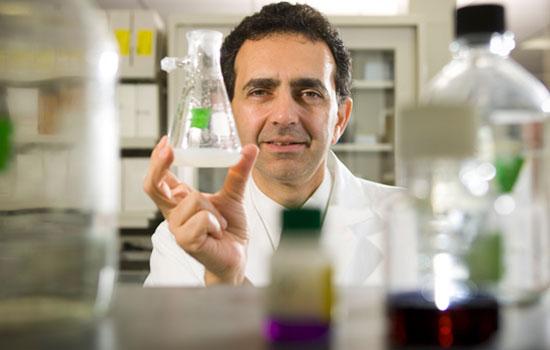 Anthony Atala looks at a beaker