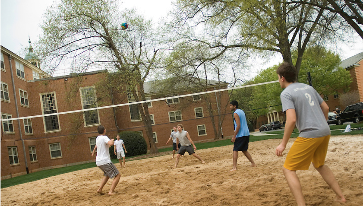 Students playing volleyball on sand courts