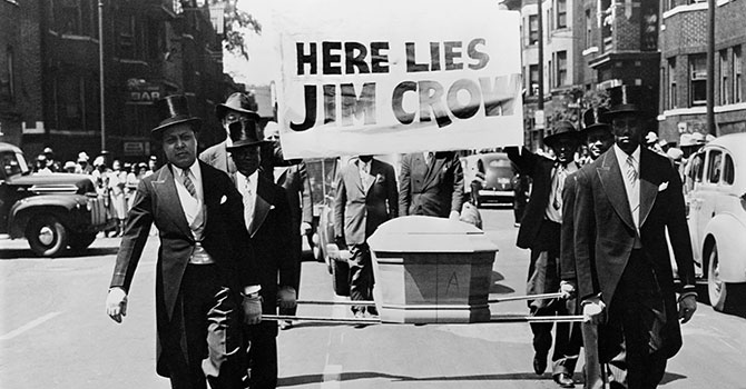 """This photo depicts a symbolic funeral of Jim Crow. The African-American men are wearing tuxedos while carrying a coffin and a sign saying """"Here Lies Jim Crow"""" as a demonstration against """"Jim Crow"""" segregation laws in 1944."""