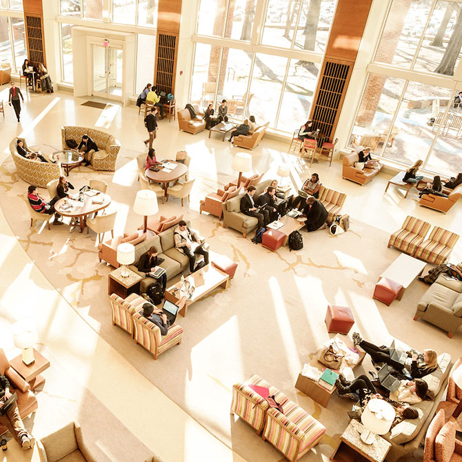 Wake Forest business students work in the atrium of Farrell Hall.