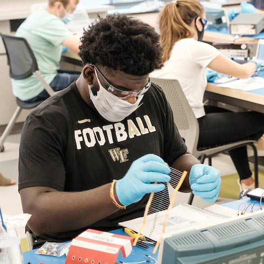 Wake Forest engineering students work on circuits with capacitors