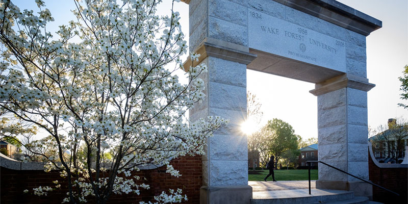 A student walks past the arch on Hearn Plaza on the campus of Wake Forest University