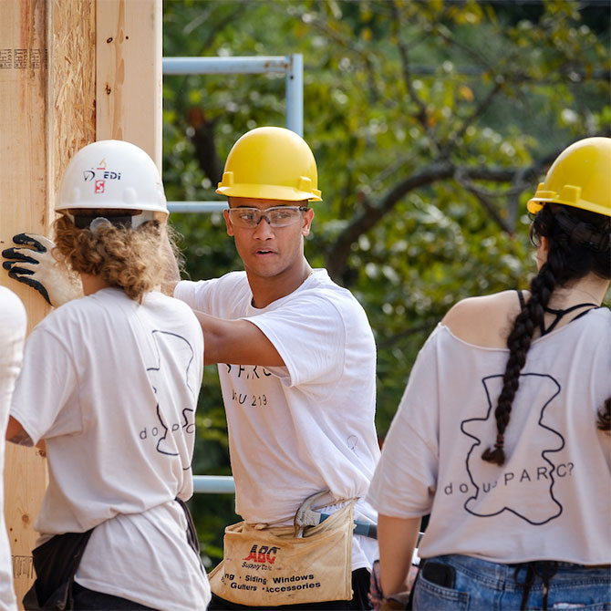 Wake Forest students in the SPARC pre-orientation program lay out and install pre-made wall sections at a Habitat for Humanity build site.