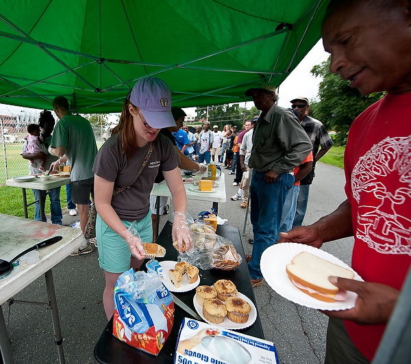 Wake Saturday's Kate Culbreath serves muffins and pastries, donated by Camino Bakery, to the homeless and needy