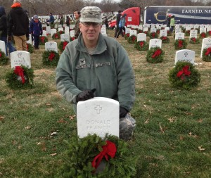 Col. Waters places a holiday wreath at a gravesite in Arlington National Cemetery.