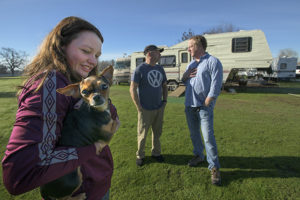 "Zada Evans 18, left with her dog ""Little Bit,"" and her father Thomas Evans talk with Woody Faircloth of Denver, Col. in Durham, Calif. on 1/27/19. Property owners Kim and Henry Young have allowed about a dozen families displaced by the Camp Fire – including the Evans – to live on their property in RVs donated through the efforts of Faircloth."