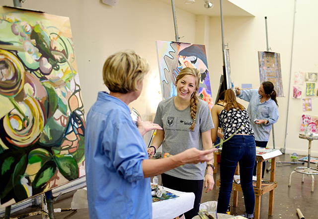 Studio painting class led by Page Laughlin, art department chair and professor of painting, September 2014. A student smiles at Laughlin gesturing in front of paintings on the wall and easels.