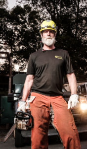 Jim Mussetter stands in his orange work chaps and wearing a helmet and holding a chainsaw.