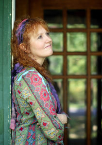 Jeanette Sorrell in a print dress and hairband gazes up as she leans against a doorway at her home.
