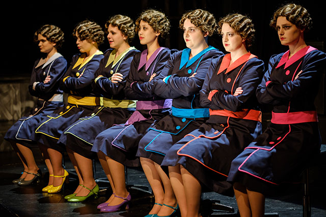 "A row of women in bobbed curvy 1940s hairdos in colorful uniforms sit primly in chairs in a dress rehearsal for ""The Adding Machine,"" directed by Professor Brook Davis, on the Tedford Stage, February 2018."