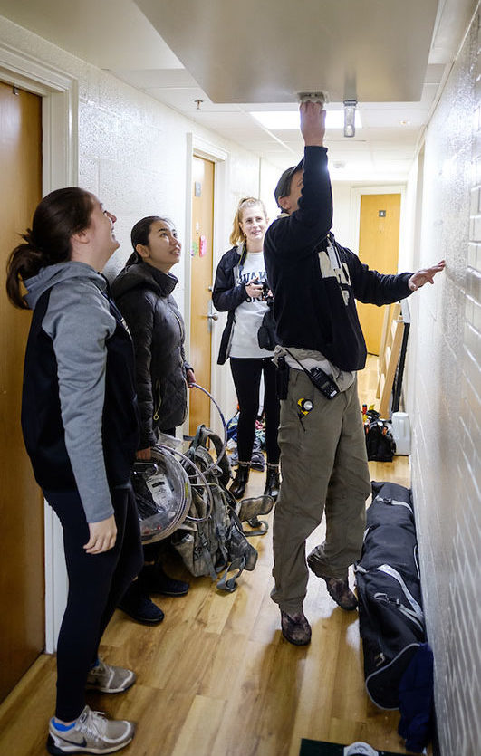 The three students shadowing electrician Rob Hager watch as shows them how to change out lights in a dorm hallway as they stand amid cords and other equipment.