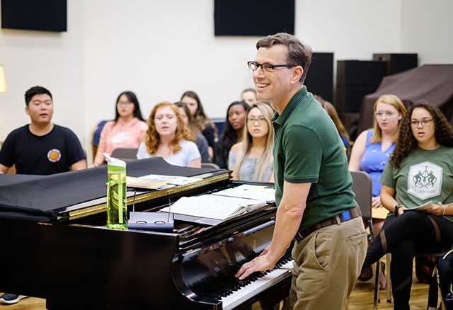 Standing at a piano in front of students, Wake Forest Associate Professor of Music Brian Gorelick (P '17) teaches the concert choir class in Scales Fine Arts Center, September 2019.