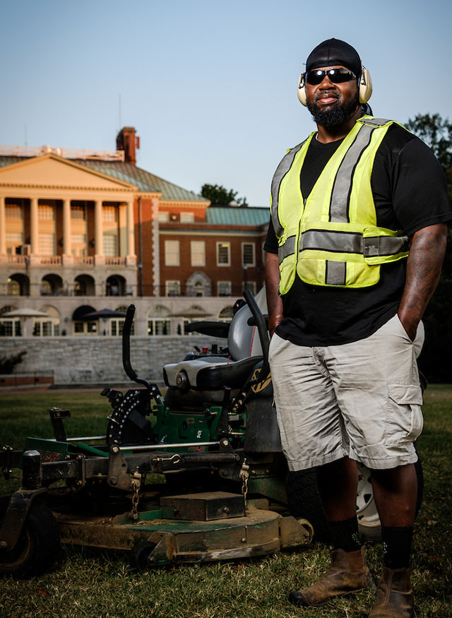 Landscaper Chris Boston poses on Manchester Plaza, wearing a yellow vest and headphones, next to his mower.
