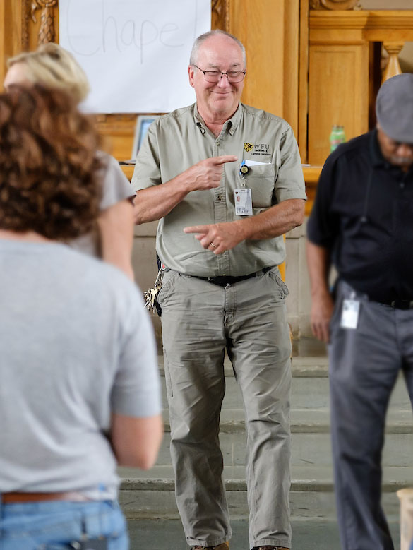 Hugh Brown (P '09), a master carpenter with 37 years on campus, stands with a sly smile on his face and points one hand in one direction and the other in the other direction, joking about which way to go.