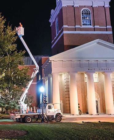 "Scenes ""From the Ground UP,"" a Telehandler bucket truck lifts an arborist to the top of a tree next to Wait Chapel"
