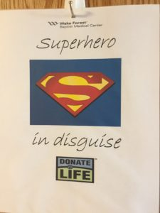 a sign says Superhero in disguise with a Superman logo