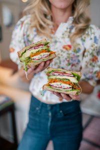 Ashton Keefe holds two giant sandwiches.