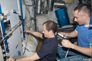 NASA astronaut Tom Marshburn (at left), Expedition 34 flight engineer, looks into a mirror as Russian cosmonaut Evgeny Tarelkin, flight engineer, gives him a hair trim in the Tranquility node aboard the International Space Station.