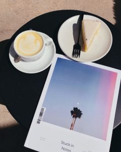First issue of Stuck in Notes magazine with cover of solitary California tree and moon on a table with a cup of latte and a plate with cheesecake and fork shot from above on a black placemat
